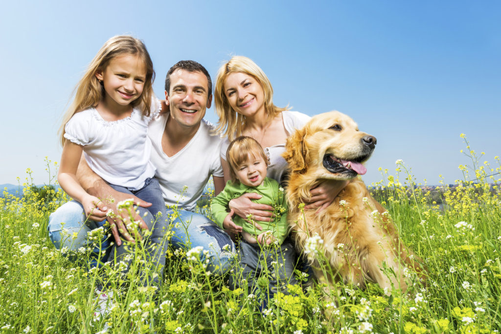 Happy family with a golden retriever.